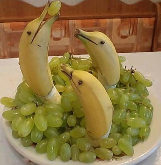 Cut bottom half of banana peel off the banana, then cut the stem and part of the top of the banana in half.  Arrange grapes on a plate and place the exposed banana vertically in the grapes.