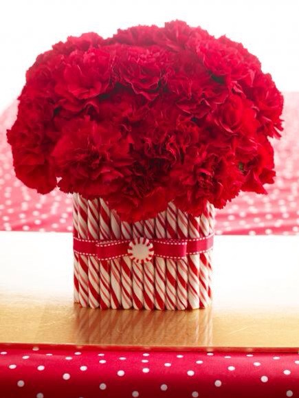 Red and white cheer  Carnations top a rectangular glass vase covered with candy canes. Attach candy canes to the vase with a hot-glue gun; anchor flowers in floral foam. If you like, spray canes with coats of clear acrylic spray to avoid stickiness. Finish with ribbon and mint.