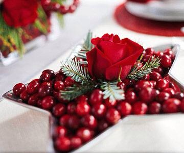 Berry red display  Fill a bowl with red cranberries, and stick a single red rose in the center. Put the stem in a florist's water tube to keep the flower fresh. A few evergreen sprigs provide accent color.