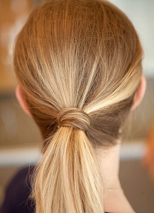 8. Cover the elastic of your ponytail with a section of hair pinned around the base. After you've tied off your ponytail, grab a small section (about the width of your pinky) from the tail and wrap it around the base. Tuck in any loose ends and secure it by inserting a bobby pin into the base.