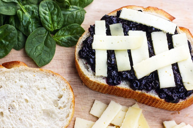 2. Spread blueberries onto a piece of bread, top with cheese, some spinach, then more cheese! Sprinkle with fresh ground pepper. Top with your other slice of bread and toast. Enjoy!