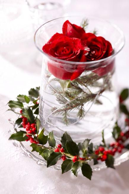 Easy and elegant  Create this pretty centerpiece in just a couple of minutes. Float roses and a few evergreen twigs inside a clear container, and surround with holly. Build on a clear tray or platter, and you've got an easily portable decoration!