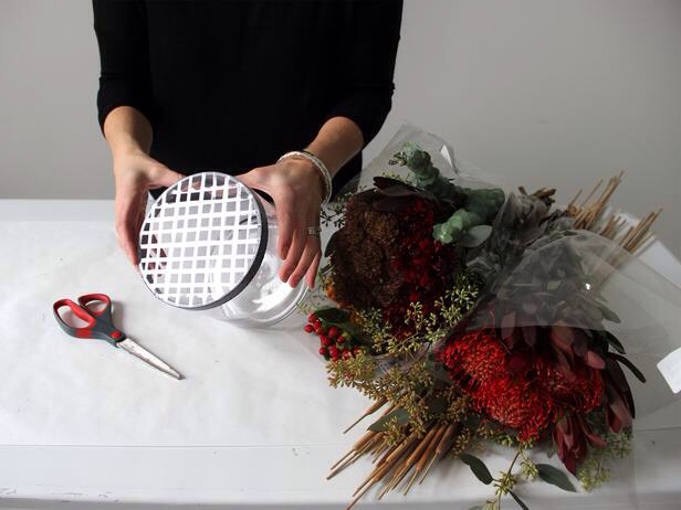 Prep the Vase for Flowers This tutorial from Made + Remade explains exactly how to arrange a grocery store bouquet. Add water to the vase and then tape off a grid using double stick tape.