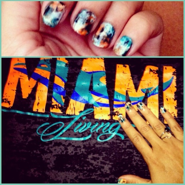 Miami Dolphins inspired Water color nails. Choose a base, then put drops of other colors. With plastic sandwich baggie, put on your wet nail and smear colors together.