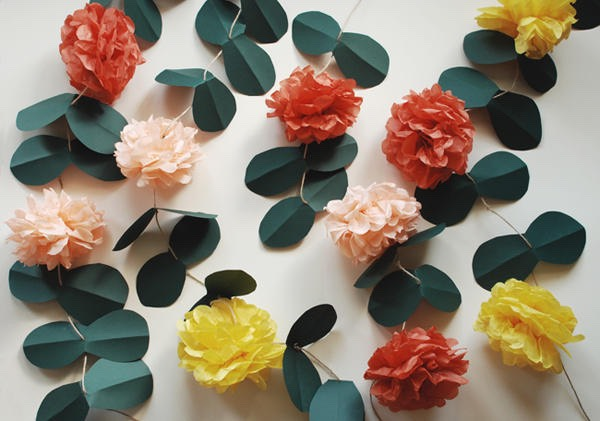 This project is a simple twist on a pom pom garland by stringing them vertically with paper leaves so they become vines. You can hang them in trees or tie them to a strand across a ceiling to fill up a room.  Customize your own by using different colored tissue paper, and different leaves n flowers!