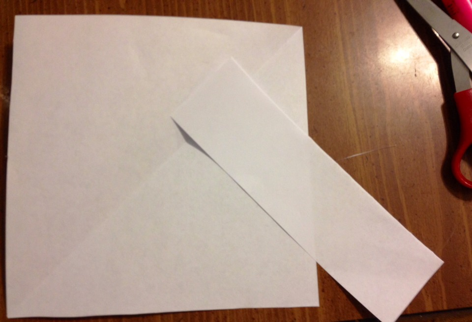 Fold the paper the make a square and then cut off the extra strip. You'll need both pieces so don't throw it out.