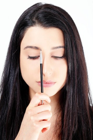 STEP 1  Place a brush along the side of your nose to find where your brows should ideally start.
