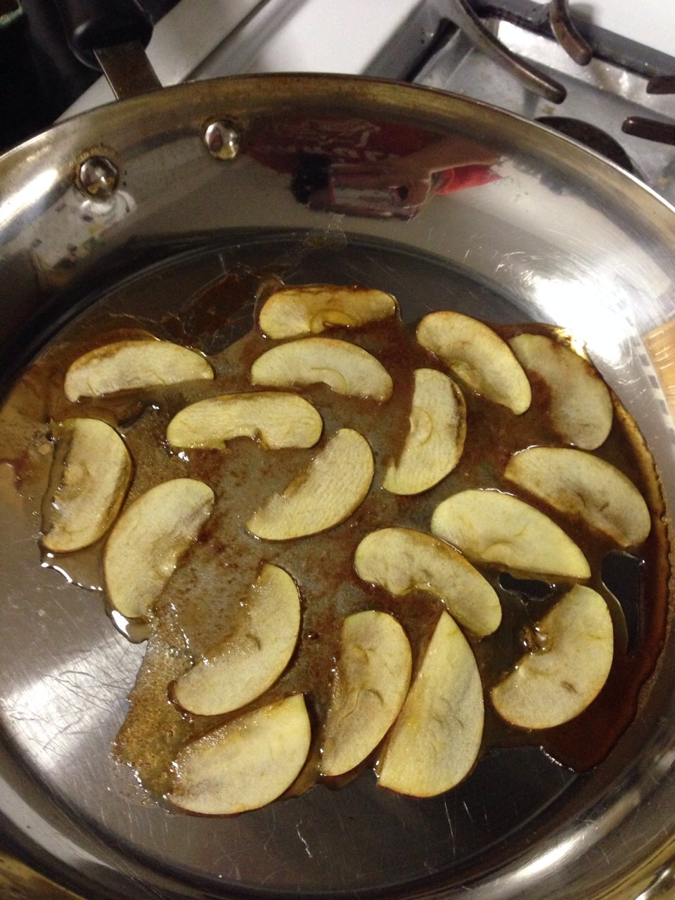 Mix the sugar and cinnamon together  Add a few table spoons of water until you get a thick dark syrup Caramelize the slices of apple with the syrup.  Make sure each slice fully touches the surface of the pan. Try to keep the slices in tact.
