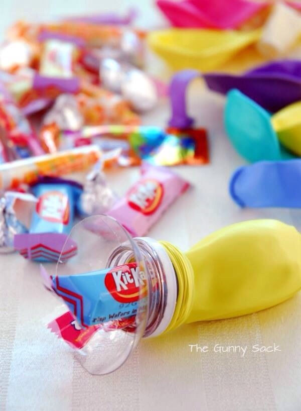 Cut top off a soda bottle. Next take party balloons and place balloon opening around tip of soda bottle. Insert candy and when the time is right let the kids pop the balloons for a sweet surprise!!!