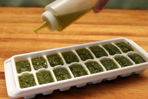 Use a squeeze bottle or spoon to drizzle a light layer of olive oil over the top of each cube compartment. This will keep the pesto from getting dark from contact with the air.