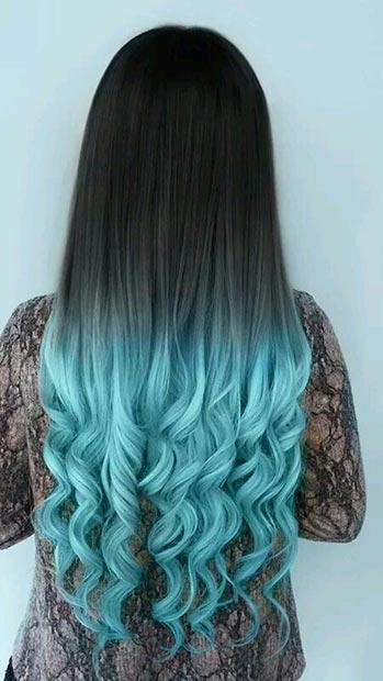 BLACK HAIR WITH LIGHT BLUE TIPS: These fun, light blue tips are a great way to spice up your long tresses. The look is a unique and modern twist on ombre. We think that her romantic curls look even better in this gorgeous shade of blue.