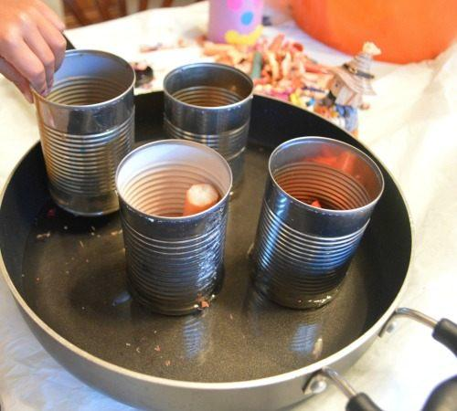 We set up a double boiler system. We poured water in a large deep pan and placed all the tin cans containing the candles and crayons in there.With a medium flame we let the crayons and candles melt.