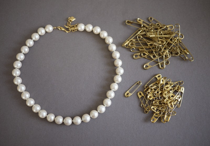You'll need: -a pearl necklace -a handful of 1 1/8″ gold safety pins -a handful of 1 1/2″ gold safety pins