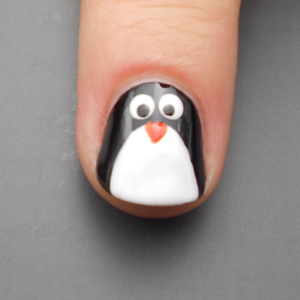 Step 5:  Use bright orange nail polish and a tiny paintbrush to paint the penguin's little beak. I used Barry M Block Orange.