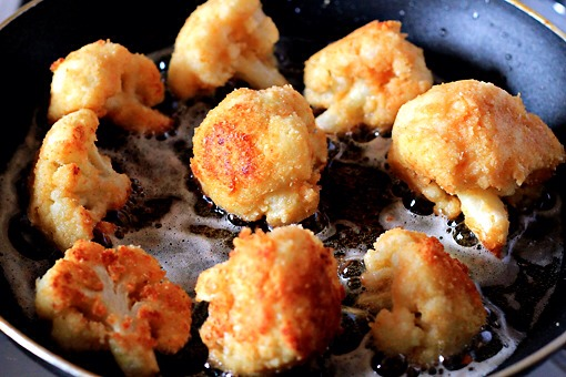 14. In batches, put the cauliflower in the preheated pan and fry it. Turn the florets so that they get golden-brown on all sides.  This process takes about 5 minutes.