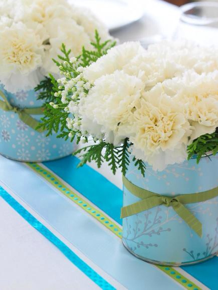 Easy flower arrangement  Create your own customized flower composition by covering coffee cans with wrapping paper and embellishing them with ribbon. Fill with inexpensive white carnations and baby's breath, plus evergreens cut from your yard.