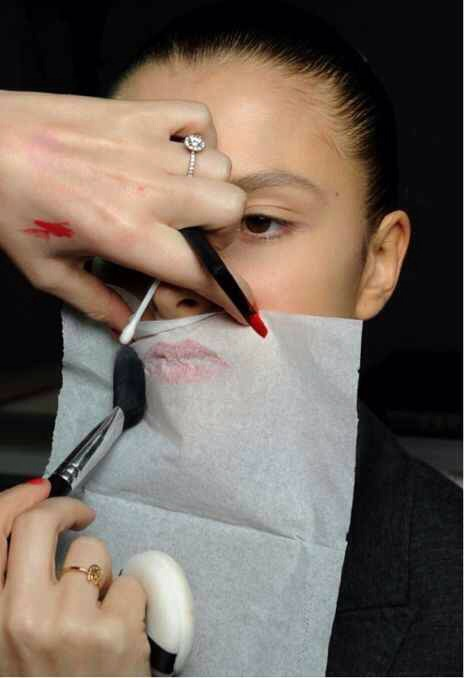 After you have applied your lipstick, hold a tissue over your lips and lightly dust translucent powder over the tissue.