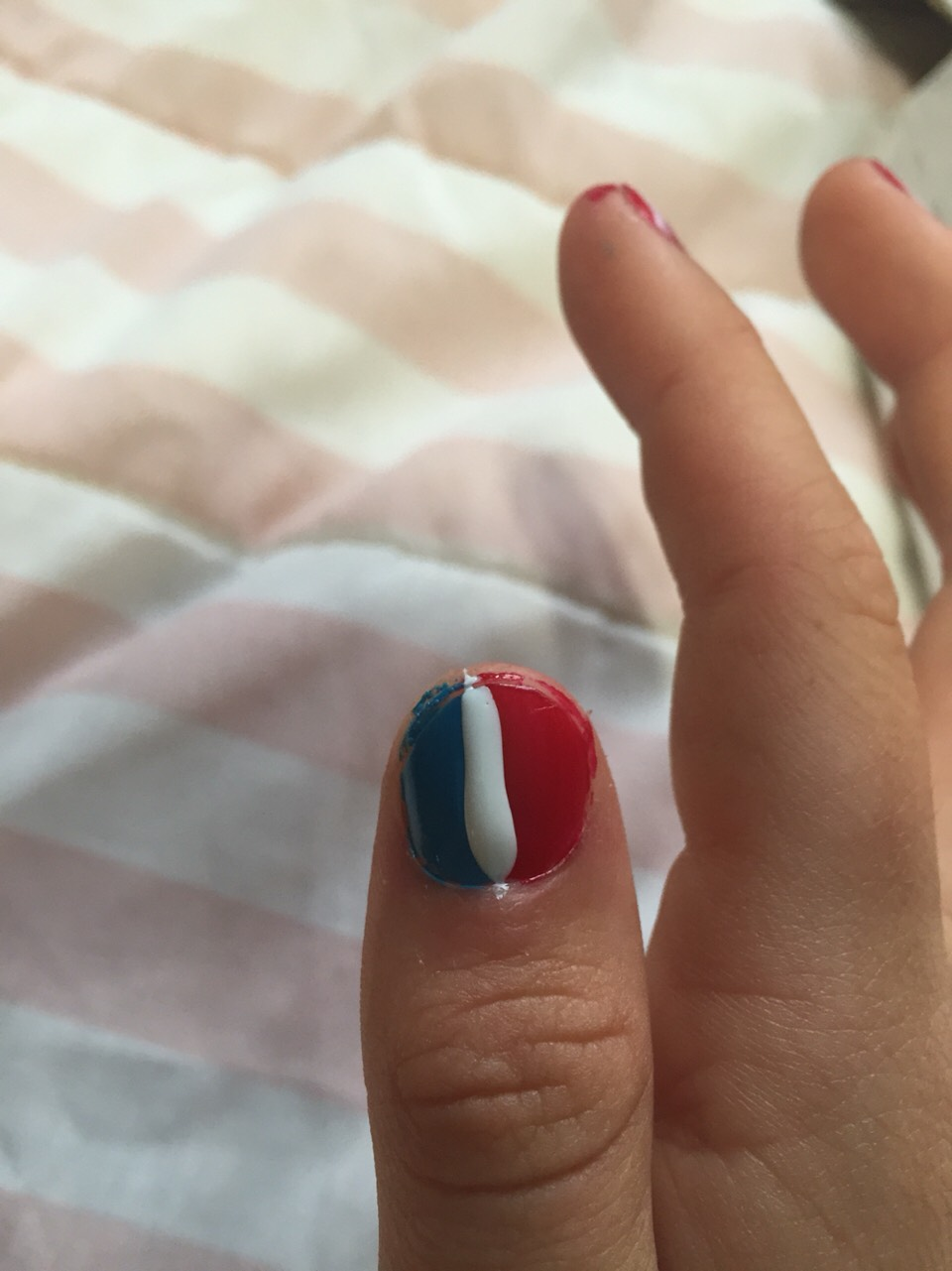 Make a white stripe with a think white brush between the red and blue polish