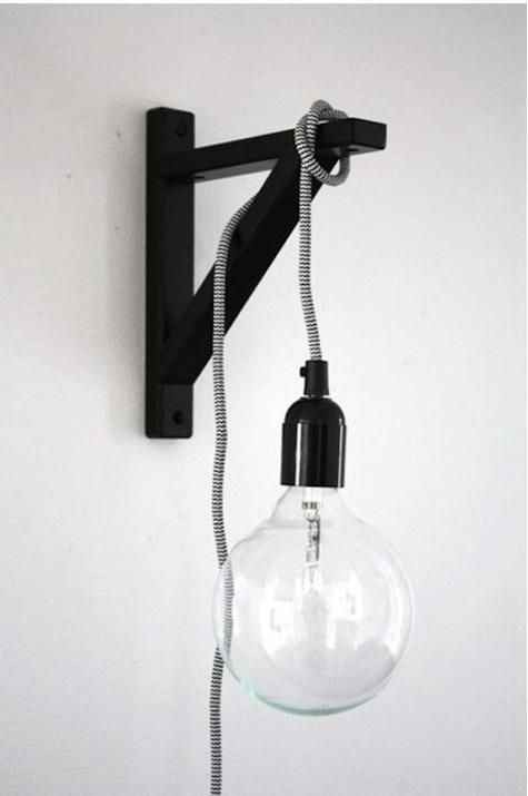 For a space-saving lamp, hang a lightbulb on a cord off of a wall-mounted shelf bracket. Pls tap for full view.