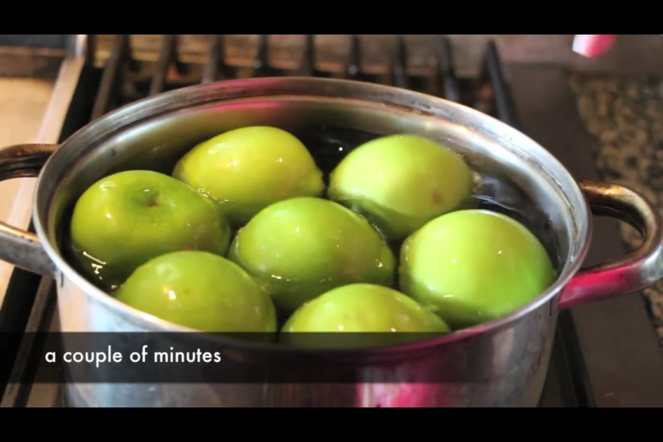 Place apples in hot water for a few minutes to remove wax.