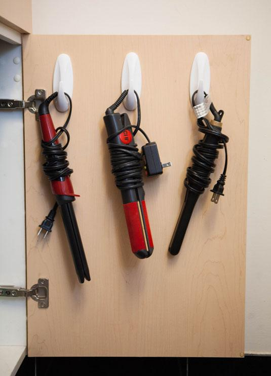 Hang your hot tools on adhesive hooks inside of a cabinet door.