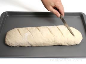 Pinch edge of dough into roll to seal. Roll gently back and forth to taper ends. Place both loaves on cookie sheet.Cut 1/4-inch-deep slashes across tops of loaves at 2-inch intervals with sharp knife. Brush loaves with cold water.