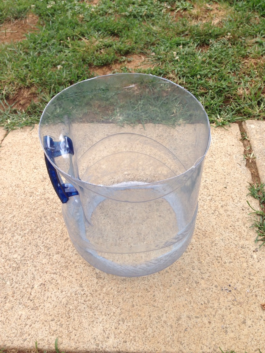 Cut top off of water jug to the height you need for your dog to eat comfortably, using shears.