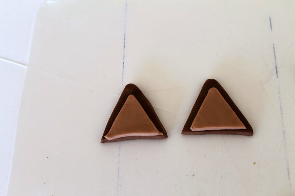 Cut out two triangles of contrasting colours for ears and place them ontop of the cake to the sides.