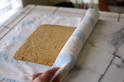 Starting at the short end of the cake, fold the towel over the edge, then gently roll the cake up in the towel. Try to roll it tight.