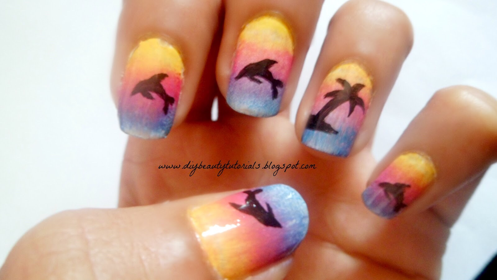 Simply use a sponge for an ombré effect and then use a nail pen to make the dolphins!