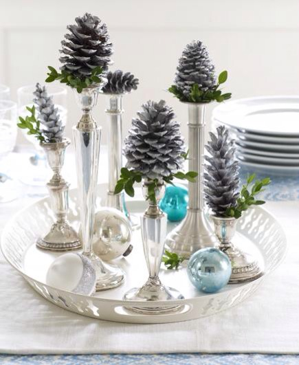 Make candlestick cones  Top silver candlesticks with silvery painted pinecones for an elegant display. Group several on a tray, and add some blue or silver ornaments for even more impact.  To paint pinecones, apply several thin coats of metallic silver spray paint.
