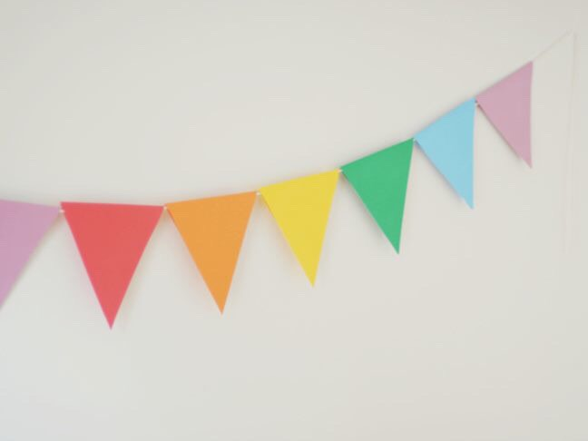 "6. Buy some patterned and solid card stock, a hole puncher, and a thick woven string to make your own pennant banner. Punch two holes in each ""pennant"" and weave the string through."