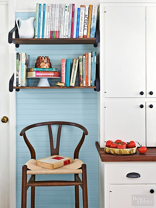 Don't ignore Nooks.  Shelves don't need to be long expanses of horizontal space to be useful, especially in small spaces. Here, a narrow nook with narrow shelves yields a storage bonanza for cookbooks.