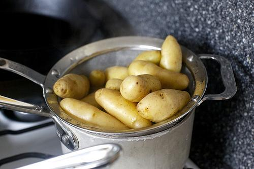Meanwhile, cook potatoes: In a separate saucepan, cover potatoes with 1 to 2 inches cold water. Set timer for 15 minutes, then bring potatoes to a simmer. When the timer rings, they should be easily pierced with a toothpick or knife. Drain and keep warm.