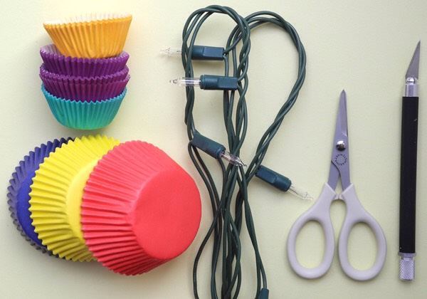 Materials you will need:  cupcake papers (large and small), string lights, scissors, and an exacto knife.