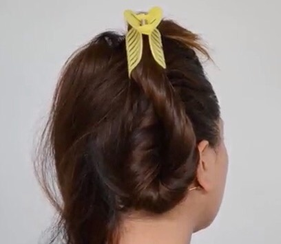 Ask someone to hold it out of the way or use a barrette/clip. Do the same thing on the other side