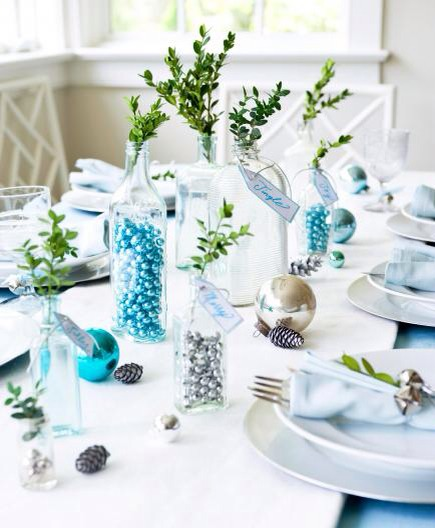 Clear glass sparkle  Create a lovely centerpiece with an assortment of clear or lightly tinted glass bottles. Fill some with small glass balls, and add a sprig of boxwood or other greenery. Everyday white dishes look fresh and elegant with a colored linen napkin on top.