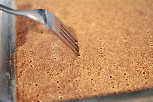 Remove the pan from the fridge. Using a fork, prick holes all over the biscuit base.