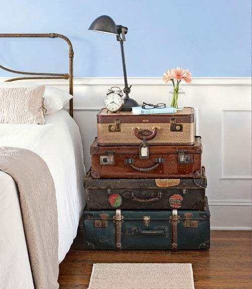 Stack a collection of old suitcases to create a makeshift nightstand.