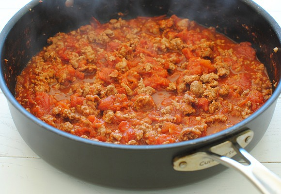 Then add the crushed tomatoes and simmer on medium until thickened, 20 minutes. In the meantime, cook the rigatoni until it's slightly underdone. Drain and rinse with cool water. Toss with parmesan cheese. Lightly oil a 9-inch spring form pan.