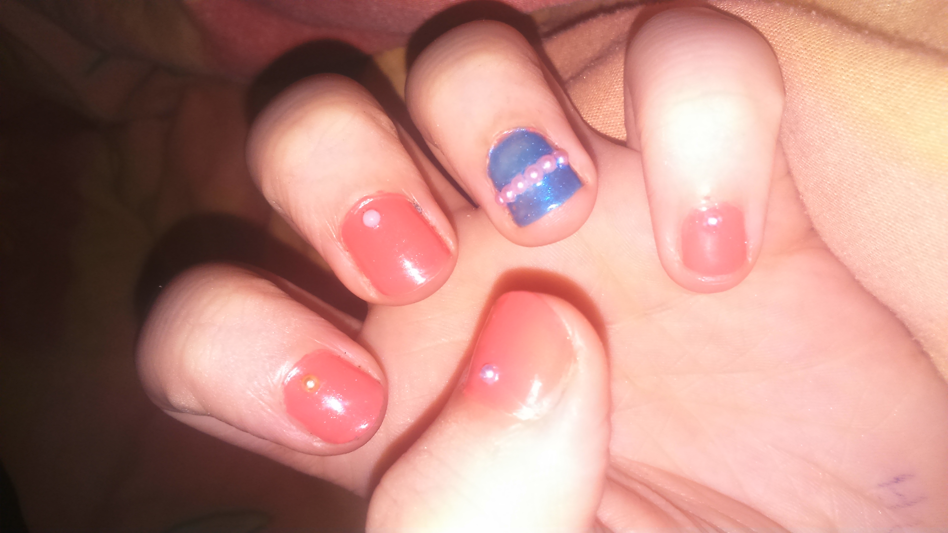 pick two nail varnish colors (mine are coral and blue) wait for them to dry and add a layer of topcoat. while the topcoat is still wet, add gems of the opposite color however you like. add another layer of topcoat and your done. simple and cute😏