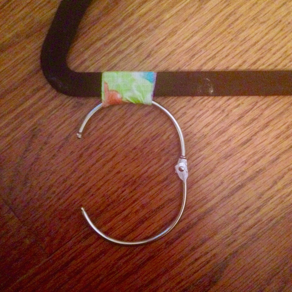 Wrap one piece of tape around each binder ring so that the ring lays flat on the ground, and is bound tightly.