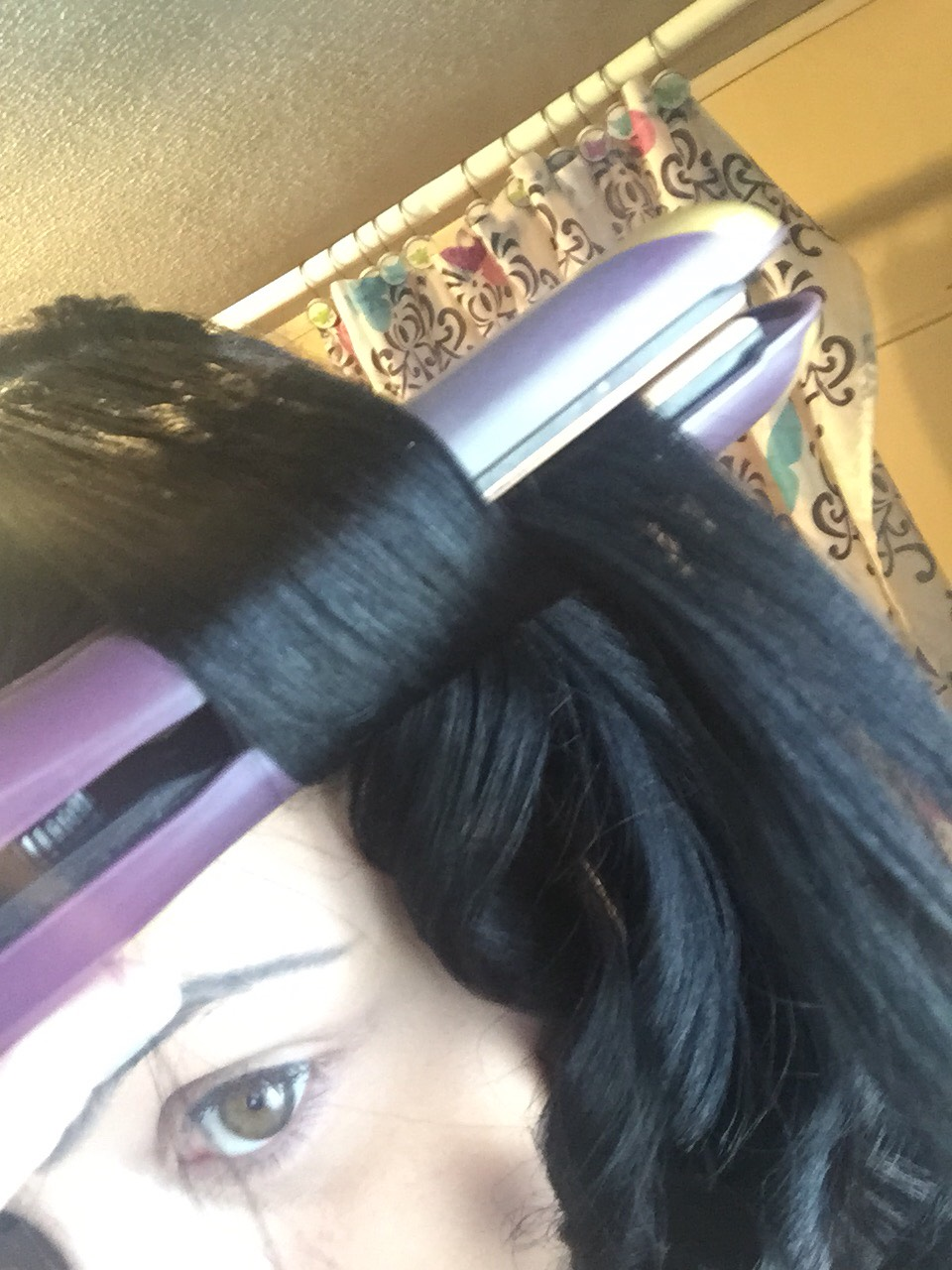 Place the piece of hair into the flat iron, as close to the scalp as possible.  I personally have thick hair, and use a 450 degree iron on my hair.  Pull the flat iron slightly away from the head and turn your wrist inward, until a portion of the hair is wrapped around both sides of the iron
