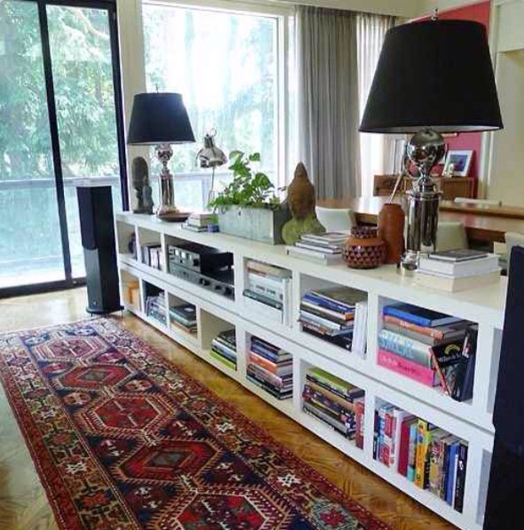 Stack Lack bookcases behind a couch to visually divide your space while also providing tons of storage!!