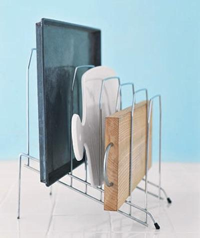 Keep your cooking pans, trays, and cutting boards in an upright position using a desk file organizer. This makes them much easier to access as opposed to having them stacked on top of each other in a pile.