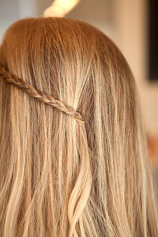 Braid a section of your hair (about the width of your pinky), and pull it back. With the open end toward your face, place one foot of the bobby pin against your head and below the braid and the other side against your head above the braid, and slide the pin forward into place.
