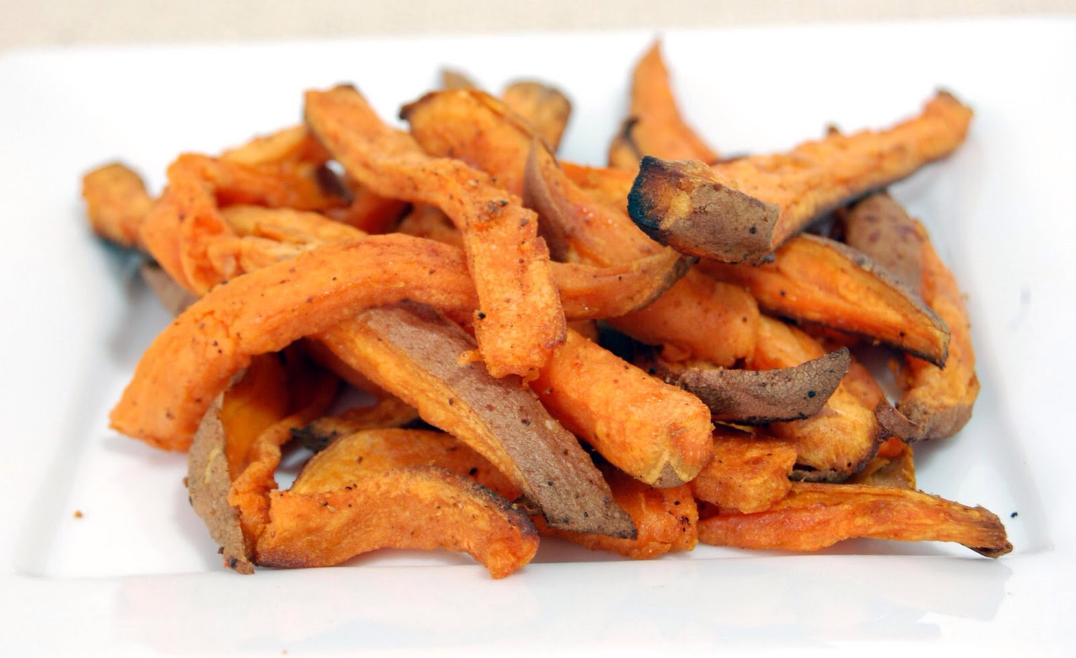 Peel the sweet potato and slice into fry shapes. Preheat oven to 425 degrees farenheight. Put the fries in a ziplock bag with enough olive oil to lightly coat the fries, a half tablespoon of salt per potato, and a tiny sprinkle of cornstarch. Shake and lay on a baking pan. Bake for 8 min each side
