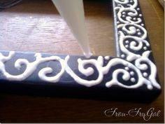 Decorate an old plain frame with glue, let it dry, then paint over it so it looks like carved wood!