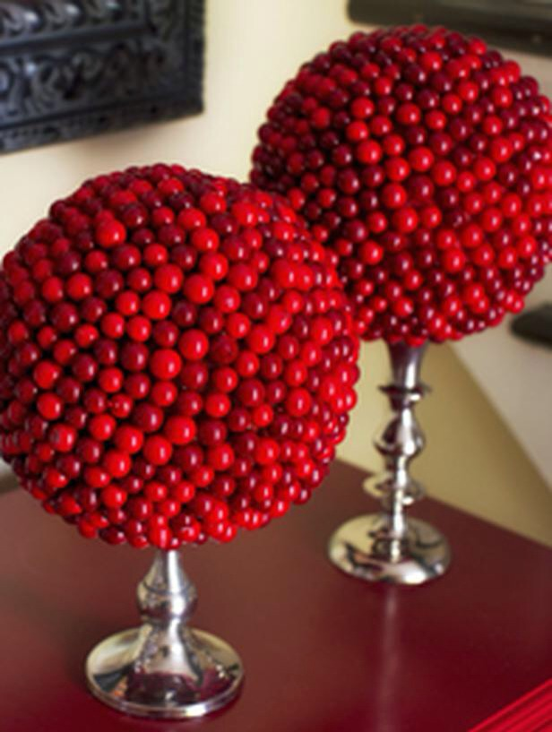 Cranberry Topiary Topiaries don't necessarily have to be made of live greenery. Create one-of-a-kind topiaries from candlesticks, foam floral spheres and faux cranberries. The graphic shape of the sphere, juxtaposed with the texture of the cranberries and sheen of the metallic candlestick!