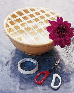 Use tape to grid off the top of the bowl and keep flowers in place